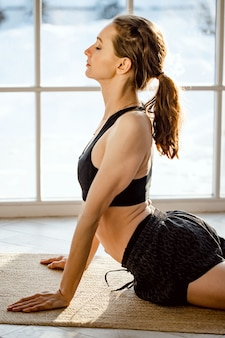 Gesunde frau in sportlichem schwarzem top und leggings beim yoga-stretching zu hause