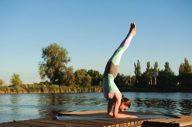 Gesunde frau lebensstil ausgewogen praktizieren meditieren und energie yoga auf der brücke am morgen die natur.
