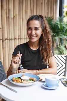 Gesunde frau mit bräune, die im t-shirt auf der caféterrasse sitzt, frühstück isst und kaffee trinkt.