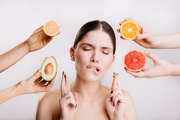 Gesunde frau posiert träumerisch mit geschlossenen augen und will köstliche orangen und avocados.