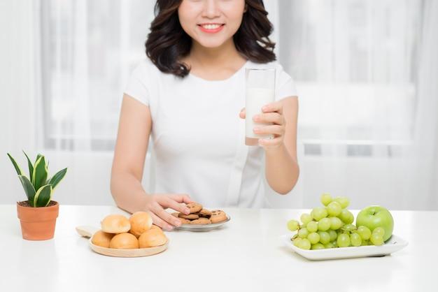 Gesunde frau trinkt milch aus einem glas isoliert auf weißem hintergrund.