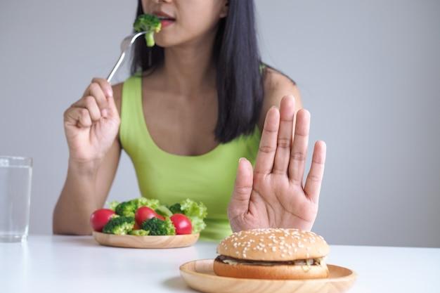 Gesunde frauen essen gemüseschalen und lehnen den verzehr von hamburgern ab.