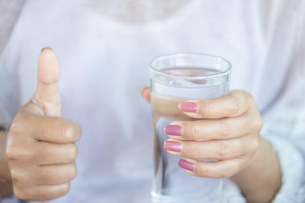 Gesunde frauenhand, die glas süßwasser hält