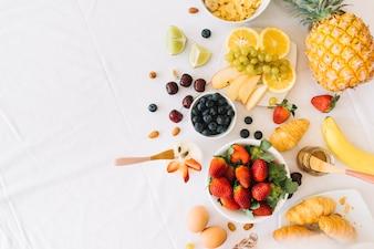 Gesunde frische Früchte mit Ei und Hörnchen auf weißem Hintergrund
