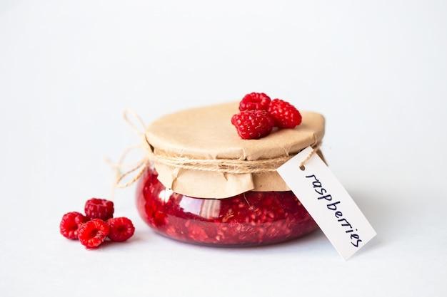 Gesunde frische himbeeren, selbst gemachte marmelade in einem glas