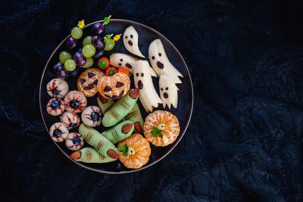 Gesunde frucht halloween leckereien. bananengeister, clementine orange pumpkins, lychee eyes und green witch fingers cookies