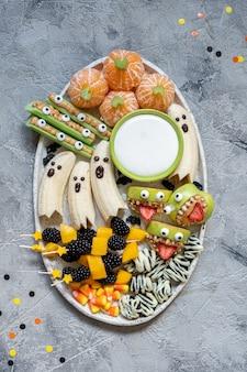 Gesunde frucht halloween leckereien. bananengeister, clementine orange pumpkins und apple monster mounts