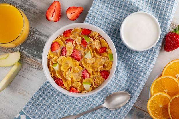 Gesunde frühstücks-cornflakes und erdbeeren mit milch