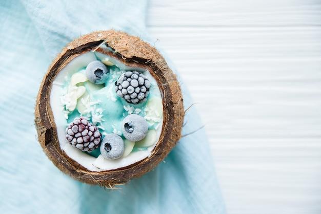Gesunde frühstücksbeere, bananen-smoothie-schüssel in kokosnuss mit blaubeeren und chiasamen, brombeeren-kokosnuss-köstliche blaubeer-smoothie-schüssel. veganes rohkost. selektiver fokus. speicherplatz kopieren