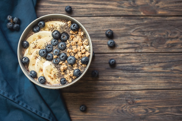 Gesunde frühstücksbeere smoothieschüssel überstiegen mit banane, granola, blaubeeren und chia samen