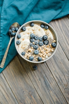 Gesunde frühstücksbeeren-smoothie-schüssel mit banane, müsli, blaubeeren und chiasamen mit kopierraum