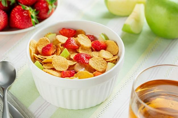 Gesunde frühstückscornflakes und -erdbeeren mit milch und apfelsaft