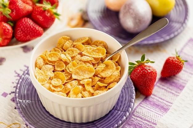 Gesunde frühstückscornflakes und -erdbeeren mit milch und gekochten eiern