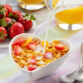 Gesunde frühstückscornflakes und -erdbeeren mit milch und orangensaft am valentinstag.
