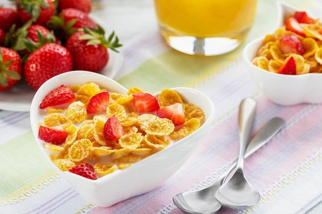 Gesunde frühstückscornflakes und -erdbeeren mit milch und orangensaft.
