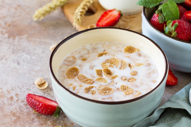 Gesunde frühstücksnahaufnahme vollkornflocken milch und frische erdbeeren auf steinhintergrund