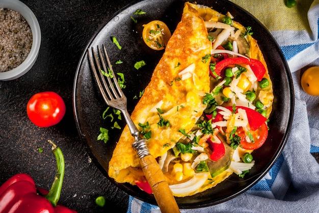 Gesunde frühstücksnahrung, angefülltes eiomelett mit gemüse