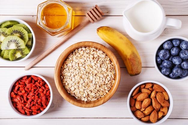Gesunde frühstücksschale mit haferflocken mit frischem obst, mandeln und honig