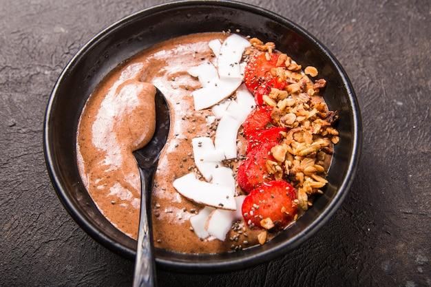 Gesunde frühstücksschale. schokoladen-bananen-smoothie-schüssel mit kokosflocken, müsli, erdbeere. draufsicht, flach liegen, oben