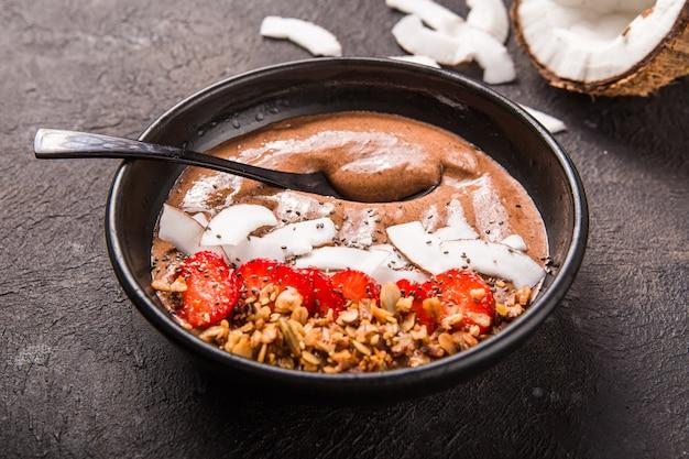 Gesunde frühstücksschale. schokoladen-bananen-smoothie-schüssel mit kokosflocken, müsli, erdbeere.
