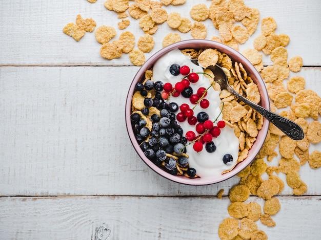 Gesunde frühstücksschüssel, cornflakes, joghurt und beeren