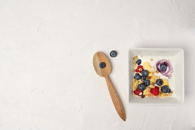 Gesunde frühstücksschüssel, cornflakes, joghurt und frische beeren auf weißen brettern. nahaufnahme, ansicht von oben, isolierter hintergrund. konzept für gesundes und leckeres essen.