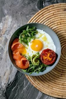 Gesunde frühstücksschüssel mit spiegeleiern, lachs, avocado, gegrillter tomate und salat, serviert mit brot auf strohserviette