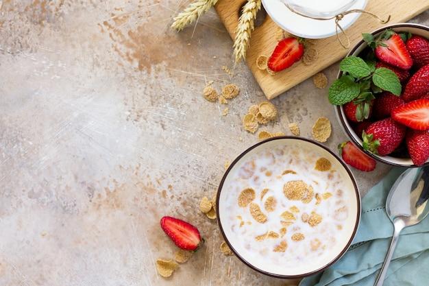 Gesunde frühstücksvollkornflockenmilch und frische erdbeeren auf stein- oder schieferhintergrund