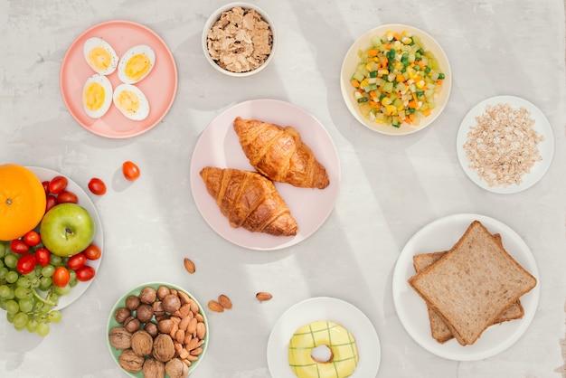 Gesunde frühstückszutaten auf schwarzem betonhintergrund. haferflocken, mandelmilch, nüsse, früchte und beeren.