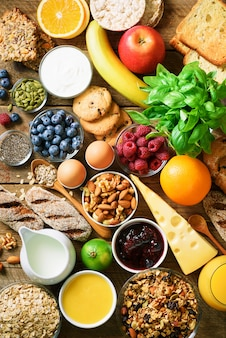 Gesunde frühstückszutaten, lebensmittelrahmen. müsli, ei, nüsse, obst, beeren, toast, milch, joghurt, orangensaft, käse, banane, apfel