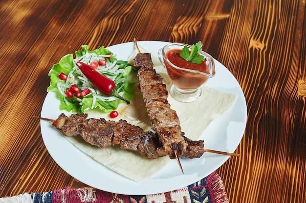 Gesunde gegrillte magere gewürfelte schweinefleischspiesse, serviert mit einer maistortilla und frischem salat- und tomatensalat, nahaufnahme