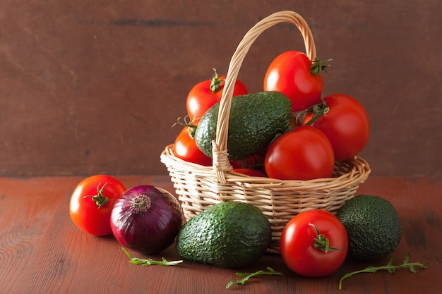 Gesunde gemüse-tomaten-avocado-zwiebel auf rustikalem hintergrund
