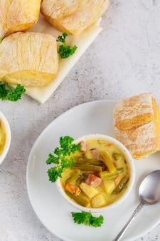 Gesunde gemüsesuppe mit brot im weißen teller. ansicht von oben.