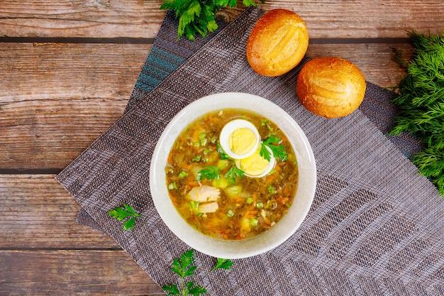 Gesunde gemüsesuppe mit ei und knusprigen brötchen