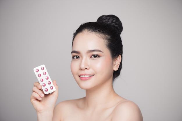 Gesunde glückliche asiatische frau mit pillen in der hand.