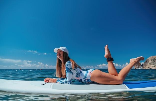 Gesunde, glückliche, fitte frau im bikini, die sich auf einem sup-surfbrett entspannt, das auf dem klaren türkisfarbenen meer schwimmt?