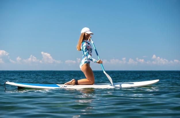 Gesunde, glückliche, fitte frau im bikini, die sich auf einem sup surfbrett entspannt, das auf dem klaren türkisfarbenen meer schwimmt