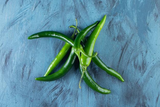 Gesunde grüne chilischoten auf blaue oberfläche gelegt.