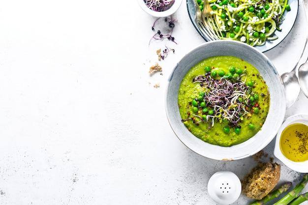Gesunde grüne erbsensuppe und zucchininudeln