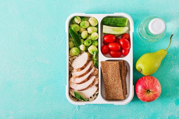 Gesunde grüne mahlzeitvorbereitungsbehälter mit hühnerleiste, reis, rosenkohl und gemüse schossen oben mit kopienraum. abendessen in der lunchbox. ansicht von oben. flach liegen