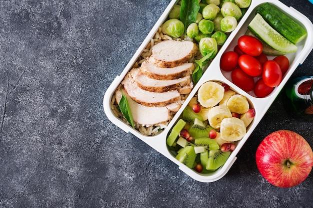 Gesunde grüne mahlzeitzubereitungsbehälter mit hähnchenfilet, reis, rosenkohl, gemüse und obst über kopf mit kopierraum erschossen. abendessen in der brotdose. draufsicht. flach liegen