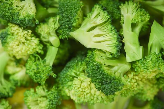 Gesunde grüne organische rohe brokkoligemüseflorets bereit zum kochen des lebensmittels - nah herauf scheiben-brokkoli-hintergrund