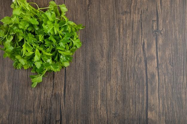 Gesunde grüne petersilienblätter auf holzoberfläche gelegt