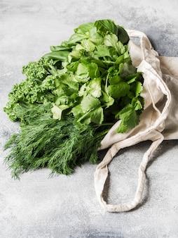 Gesunde grüne vegane zutaten zum kochen. verschiedene kräuter und keil in der textiltasche auf grauem hintergrund.