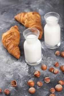 Gesunde haselnüsse in der schale mit milch und croissants auf einem steintisch.