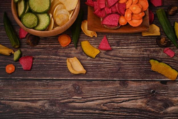 Gesunde hausgemachte gemüsechips auf holztisch.