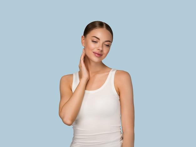 Gesunde hautfrauen der schönheit, die gesicht kosmetisches studioporträt berühren. sportswear-farbhintergrund blau