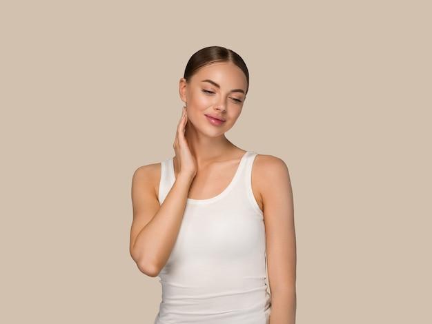 Gesunde hautfrauen der schönheit, die gesicht kosmetisches studioporträt berühren. sportswear-farbhintergrund braun
