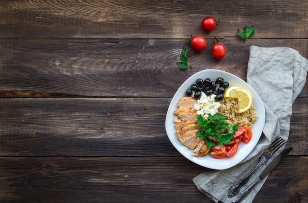 Gesunde hühner-quinoa-schüssel mit kirschtomaten, feta-oliven und petersilie auf holzuntergrund