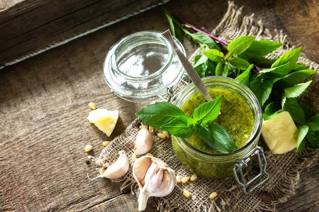Gesunde italienische küche grüne pesto-sauce mit zutaten auf rustikalem holztisch